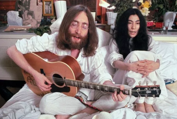 John Lennon and Yoko Ono having a bed-in sing song of love