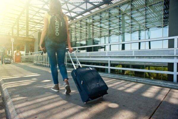 Girl with suitcase travelling in airport with a hidden money belt